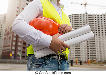 Closeup of young architect posing with hardhat and ...