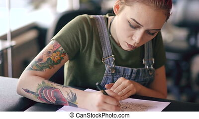 Closeup of young attractive red haired woman tattoo artist sitting at table and creating sketch for tattooing in studio indoors