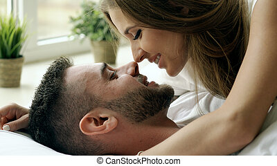 Closeup of Young beautiful and loving couple play and kiss in bed at the morning. Attractive man kissing and hugging his wife in bed
