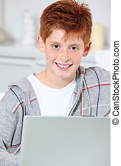Closeup of young boy at home with laptop computer