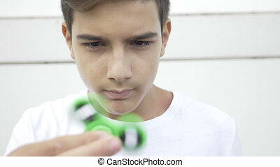 Closeup of young boy playing with fidget spinner flicking and holding the spinning device in hand