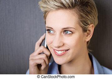 Closeup of young businesswoman using mobile phone while looking away against wall