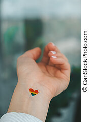 Closeup of young caucasian millennial hippie woman with painted rainbow flag in heart shape painted in wrist. Rainbow color tattoo, symbol of LGBT pride month