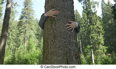 Closeup of young environmentalist woman hugging a tree thank...