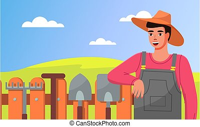 Closeup of young gardener in hat standing near fence with garden tools. Rakes, shovels, garden tools