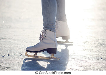Closeup of young girl on the fugure skates outdoor in sunny spring day