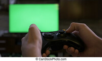 Closeup of young male hands playing on video game console controlling joystick on chroma key green screen TV screen