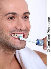 Closeup of young man brushing his teeth