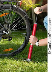 Closeup of young man pumping bicycle tyre