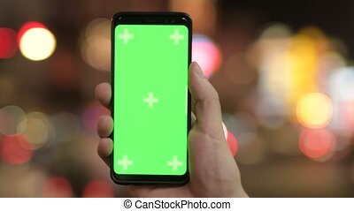 Closeup of young man using phone with green screen against illuminated lights at night