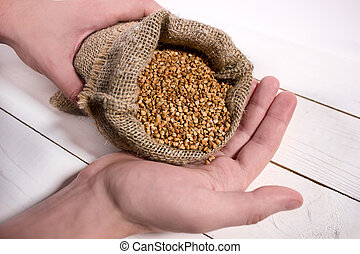 Closeup of young man's hands holding a sack with a buckwheat on white wooden table