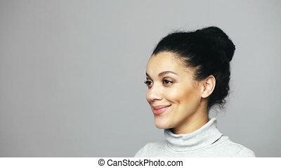 Closeup of young mixed race woman looking at camera smiling