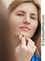 closeup of young smiling blond woman doing makeup