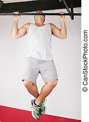Closeup of young strong teenage athlete doing pull-up on horizontal bar
