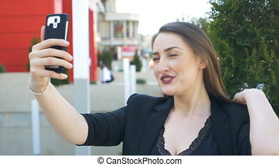 Closeup of young urban business woman taking selfie with smartphone in the city