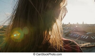 Closeup of young woman and man looking at the city at sunset standing on the roof of the house.