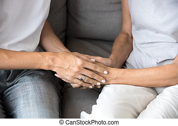 Closeup of young woman holding old female hands giving support