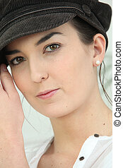 Closeup of young woman in a baker-boy cap