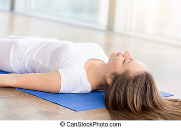 Closeup of young happy attractive woman practicing yoga, lying on blue mat in Savasana exercise, Dead Body, Corpse pose, working out, wearing sportswear, white t-shirt, indoor