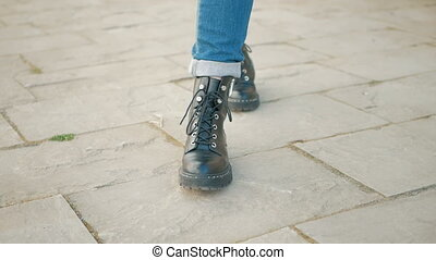 Closeup of young woman legs in black boots on cobblestone...