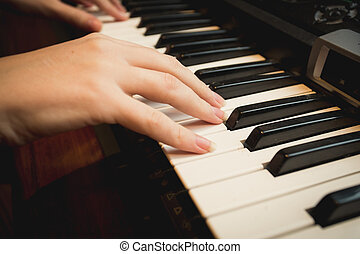Closeup of young woman playing on piano