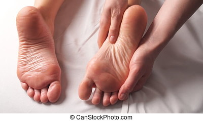 Closeup of Young Woman Receiving Professional Feet Massage in Spa Center.