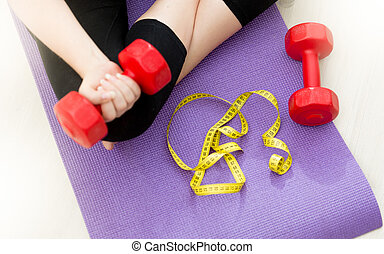 Closeup of young woman sitting on fitness mat and lifting dumbbells