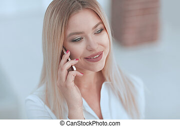 closeup of young woman talking on a mobile phone.photo on...
