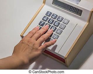 closeup oh hand with calculator on desk background