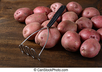 closeup old potato masher with red potatoes