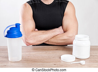 Closeup on a man with nutiotion supplements on table