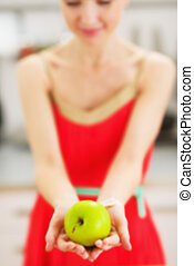 Closeup on apple in hand of young woman