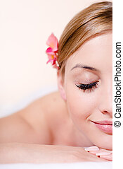 closeup on beautiful young blond woman in spa treatments happy smiling eyes closed on white background