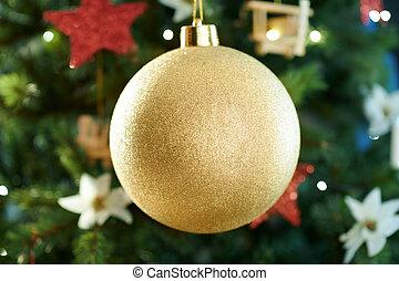 Closeup on big gold Christmas ball near Christmas tree
