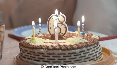Closeup on birthday cake with lighted candle in shape of ...
