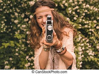closeup on bohemian young woman among flowers using retro...