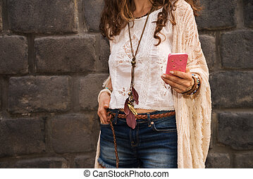 Longhaired hippy-looking young lady in jeans shorts, knitted shawl and white blouse standing near stone wall in old town and writing sms