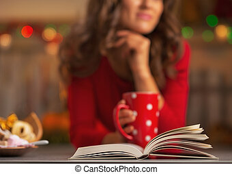 Closeup on book and thoughtful young woman with cup of hot...