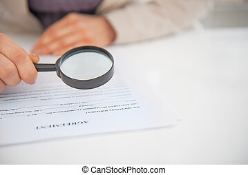 Closeup on business woman exploring document with magnifying...
