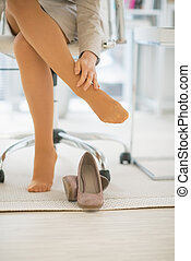 Closeup on business woman in office with foot pain