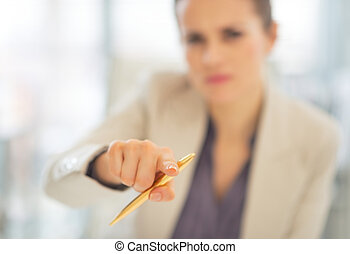Closeup on business woman pointing with pen