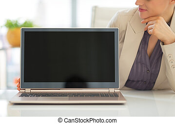 Closeup on business woman showing laptop blank screen