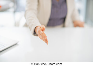 Closeup on business woman stretching hand for handshake