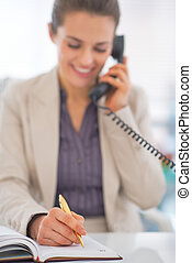 Closeup on business woman talking phone and writing in diary