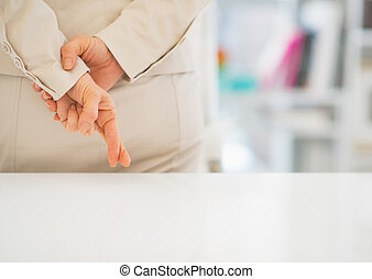 Closeup on business woman with crossed fingers
