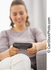 Closeup on cell phone in hand of happy young woman writing sms