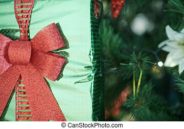 Closeup on Christmas gift in hand of woman near Christmas tree