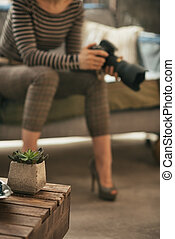 Closeup on coffee table and young woman with modern dslr photo c
