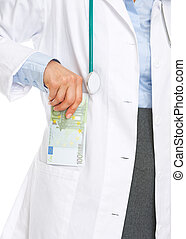 Closeup on doctor woman putting stack of euros in pocket