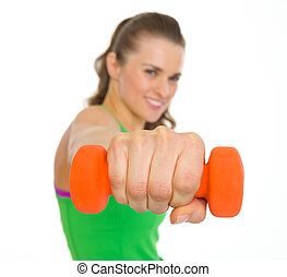 Closeup on dumbbells in hand of fitness young woman
